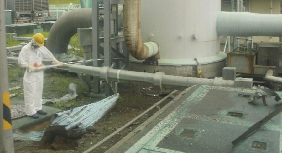 En oprydningsarbejder måler strålingen ved en ventilationsskakt på Fukushima den 1.aug. Dagen efter kunne få sekunder på samme sted slå ham ihjel.