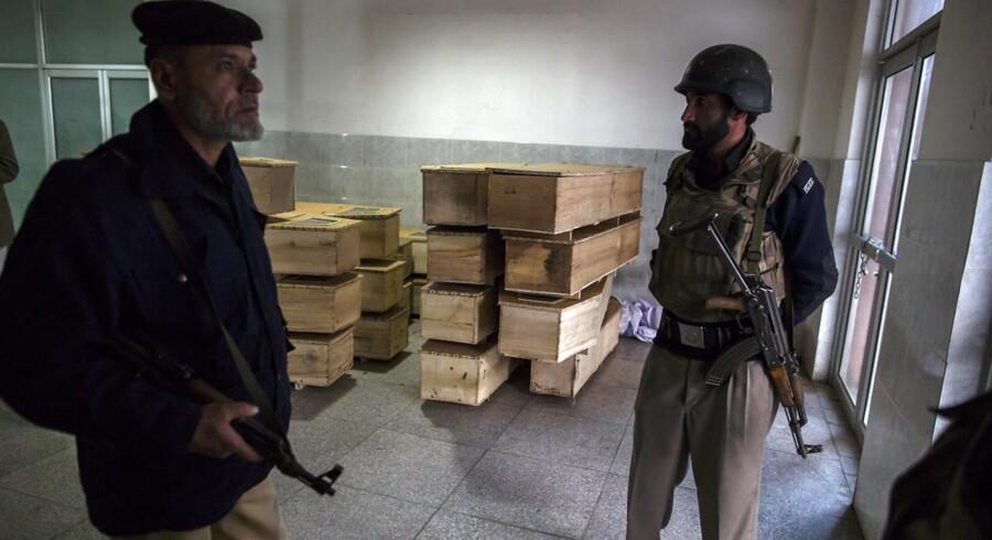 Politimænd ved siden af tomme kister på et hospital i Peshawar.