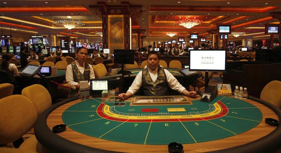 Croupierer sidder ved spillebordene på åbningsdagen i et kasino i Macau.