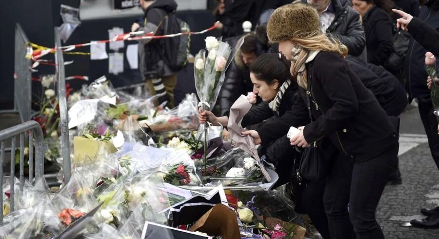 Folk lægger blomster tæt på det supermarked, hvor fire mennesker blev dræbt i en gidseltagning.