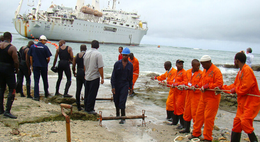 Arbejdere trækker et undersøisk telekabel i land i Kenya.