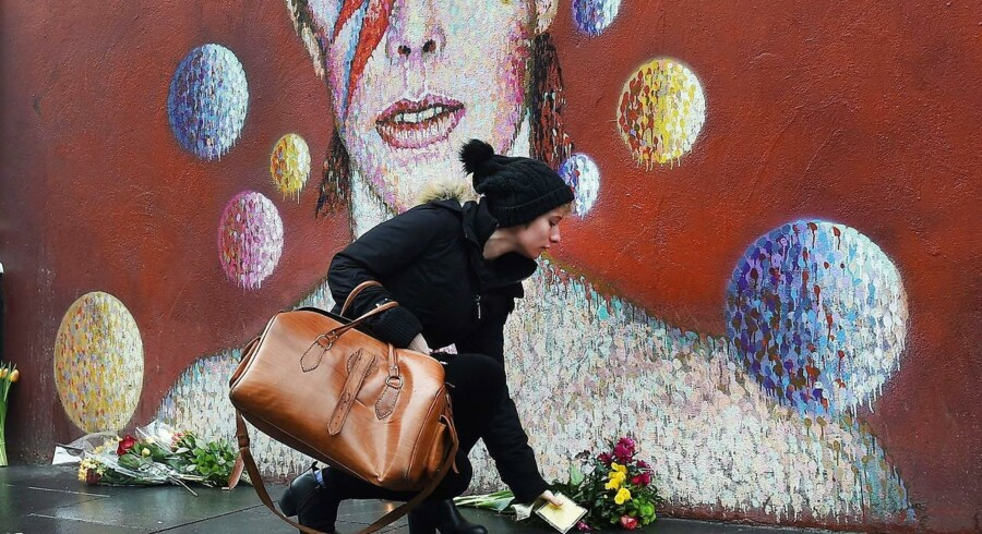 En kvinde lægger blomster ved et vægmaleri af David Bowie i Brixton, hvor den legendariske sager, som døde søndag, er født.