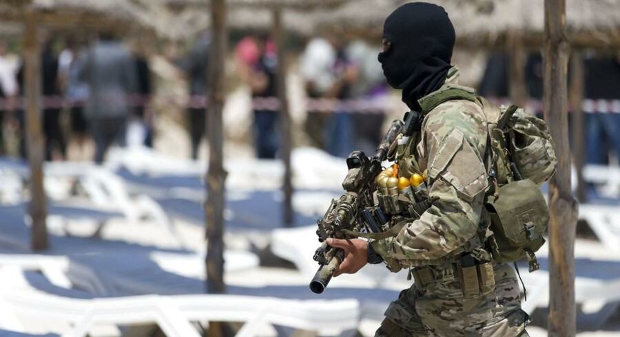 En maskeret tunesisk soldat patruljerer stranden foran Riu Imperial Marhaba Hotel i udkanten af Sousse, hvor Seifeddine Rezgui fredag åbnede ild mod strandgæsterne.