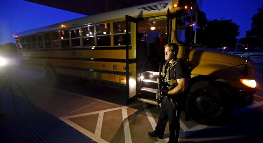 En betjent står ved en skolebus, der blev brugt til at evakuere deltagere fra The Muhammad Art Exhibit and Contest i Dallas.