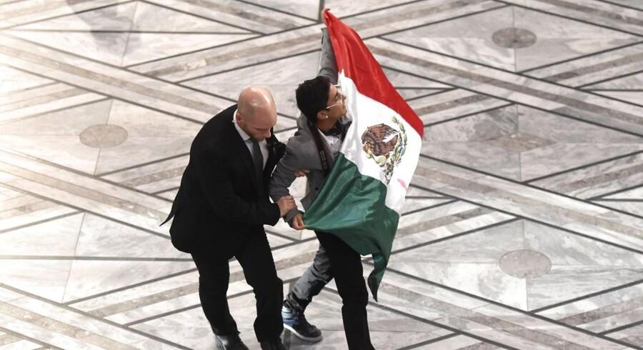 En sikkerhedsvagt blokerer en mand med et mexicansk flag, der prøver at komme på scenen under Nobel-ceremonien i Oslo, hvor Malala modtog Nobels fredspris.