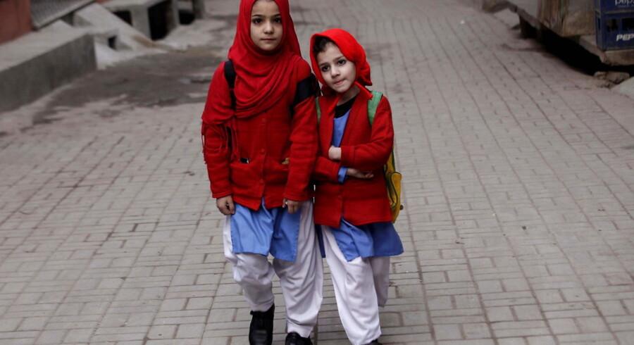 To pakistanske skolebørn på vej ud af skolen 12. januar efter genåbningen.