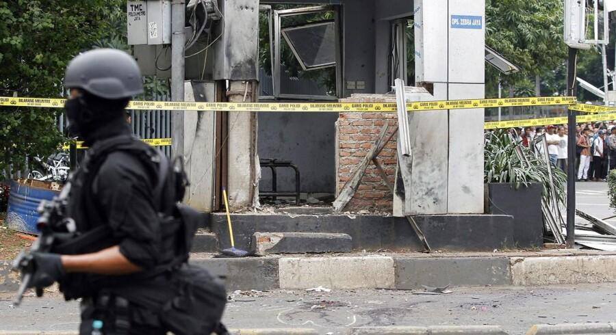 En indonesisk politibetjent ved et af de områder, hvor en bombe detonerede i Jakarta tidligt torsdag morgen dansk tid.