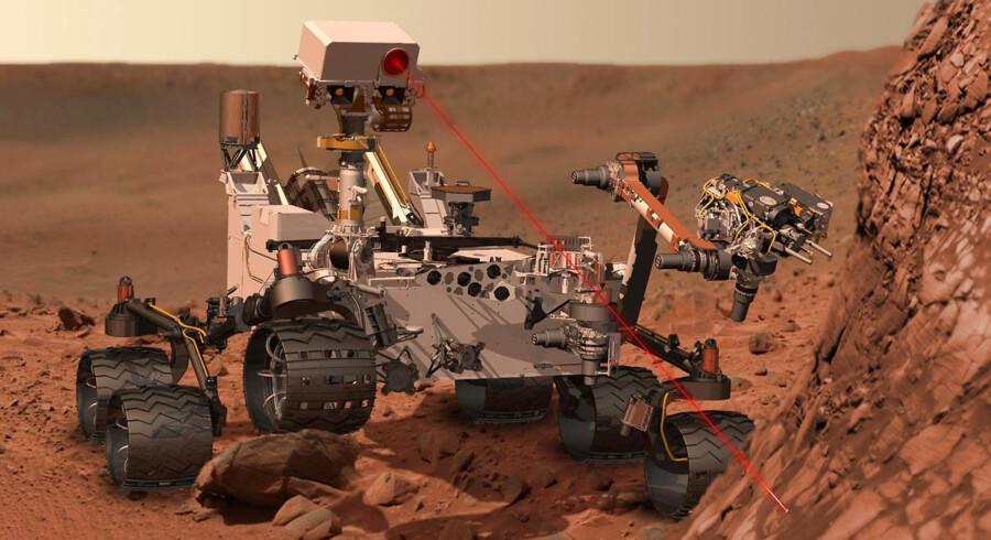 En kunstner viser her sin version af, hvordan Curiosity ser ud, når den bruger sit udstyr for at undersøge materiale på Mars. Først skal den dog lige lande på planeten.