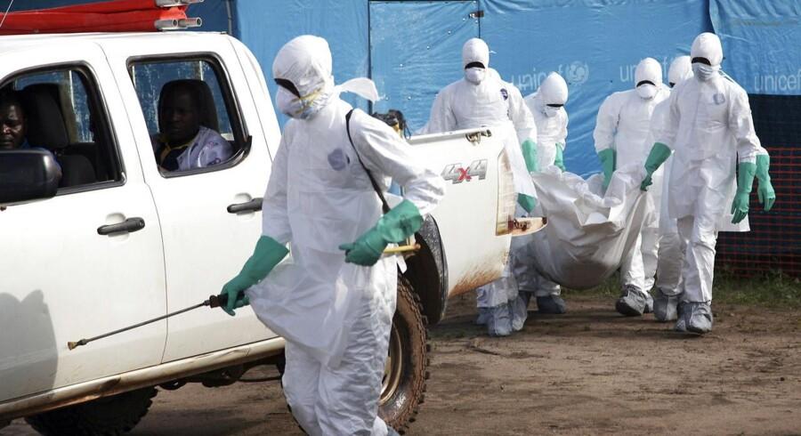 Hjælpearbejdere i Liberia er i færd med at begrave en kvinde, som er død af ebola.