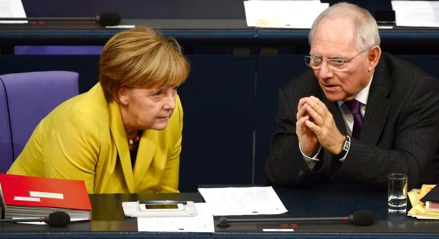 Den tyske forbundskansler, Angela Merkel (til venstre), og den tyske finansminister, Wolfgang Schäuble (til højre), er ifølge det tyske magasin Der Spiegel ikke længere nervøse for et græsk euro-exit. AFP PHOTO / JOHN MACDOUGALL