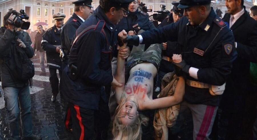 En aktivist fra Femen fjernes af politifolk på Peterspladsen.