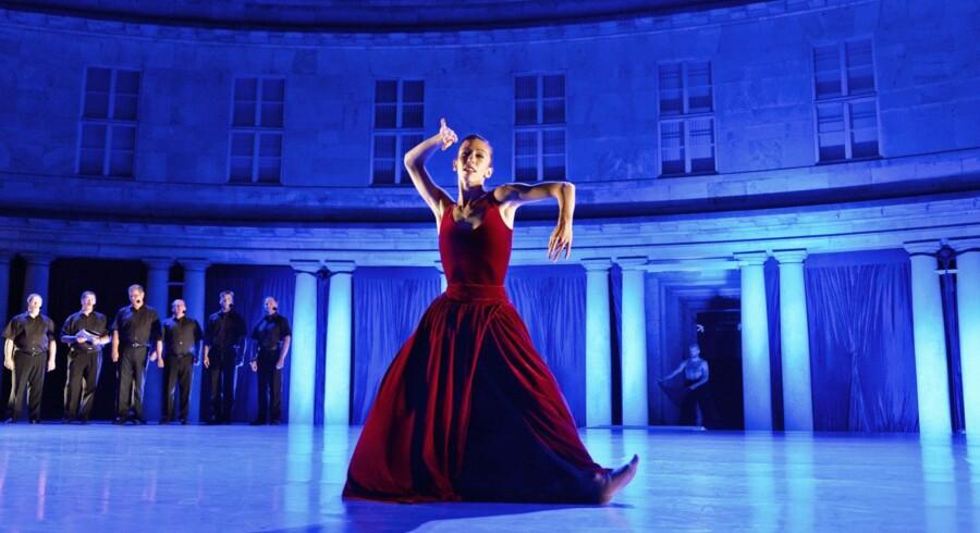 Dansk Danseteaters nye italienske danser Lucia Pasquini med det russiske mandskor Arken i baggrunden. Foto: Henrik Stenberg