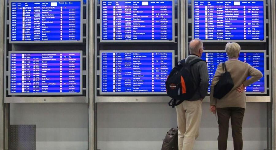 Rejsende leder efter information på skærmene i Frankfurt lufthavn, efter at mange af Lufthansas fly er aflyst.