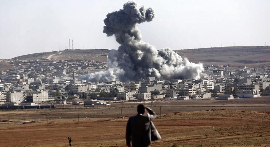 En mand ser på en eksplosion efter angreb fra den amerikansk ledede koalition rettet mod IS i byen Kobane i Syrien. Billedet er taget fra den tyrkiske grænseby Sanliurfa.