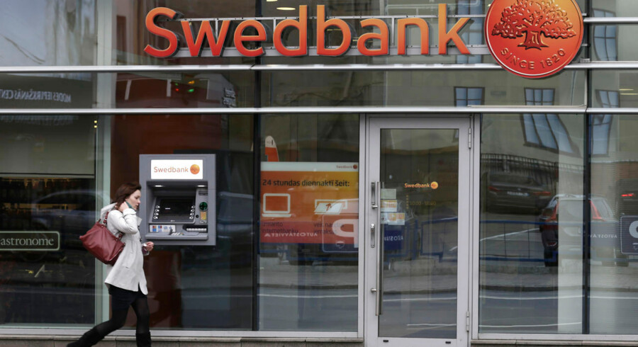 A woman walks past a Swedbank branch in Riga October 21, 2014. Banking group Swedbank said on Tuesday growth in its home markets could be dragged down by a weak global economy and political uncertainty in Sweden as it posted forecast-beating profits boosted by lending to corporate and mortgage clients. REUTERS/Ints Kalnins (LATVIA - Tags: BUSINESS)