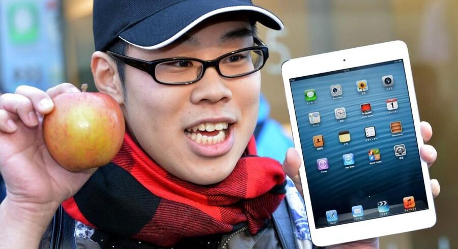 En Apple-glad japaner med sin spritnye iPad Mini i november 2012. På trods af at de japanske elektronikkæmper står stærkt i hjemlandet, er der også interesse for de amerikanske produkter i verdens tredjestørste økonomi.