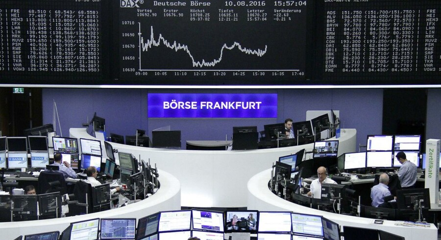 Traders work at their desks in front of the German share price index, DAX board, at the stock exchange in Frankfurt, Germany, August 10, 2016. REUTERS/Staff/Remote