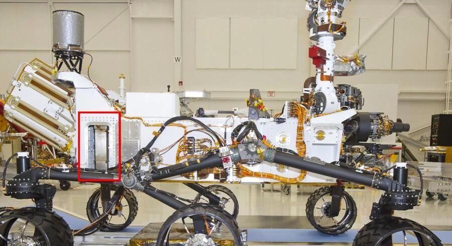 Curiosity vejer knap et ton - og er udstyret med bunkevis af avanceret eletronik og målingsudstyr. Her (den røde firkant) sidder eksempelvis et værktøj, der skyder neutroner ned i jorden. Værktøjet bruges til at lede efter vand.