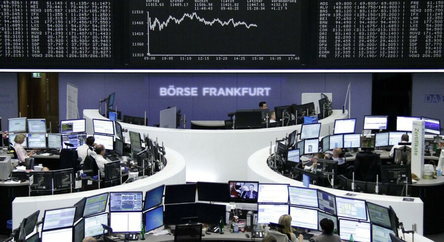 Traders are pictured at their desks in front of the DAX board at the Frankfurt stock exchange July 13, 2015. REUTERS/Remote/Staff