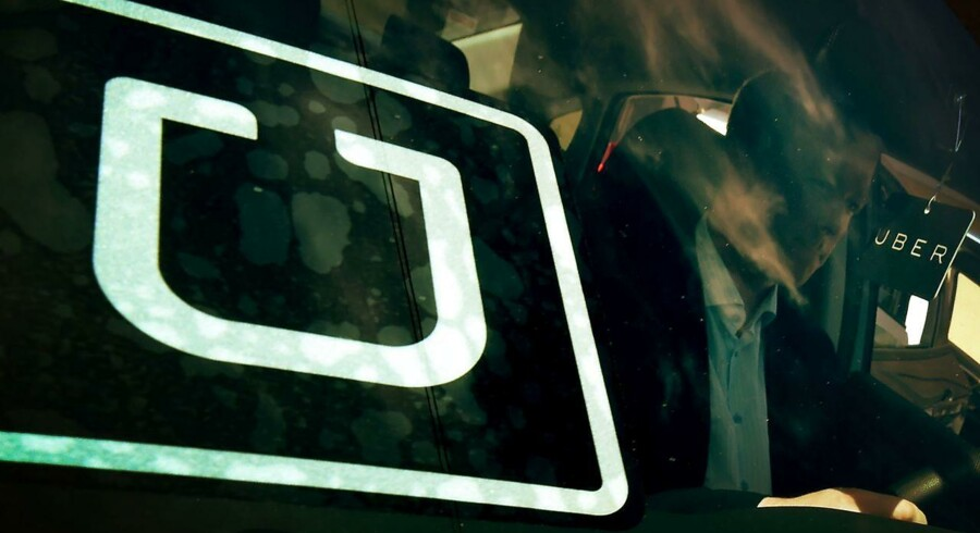 """(FILES): This file photo taken on March 10, 2016 shows a man checking a vehicle at the first of Uber's 'Work On Demand' recruitment events where they hope to sign 12, 000 new driver-partners, in South Los Angeles Uber and Lyft are eviscerating the taxi industry in Los Angeles three years after they began operating in the city, officials say. Thanks to the ridesharing services, which enable independent drivers to offer rides via a smartphone application, """"taxicab service demand indicators have dropped (total trips and dispatch trips) beginning in the second half of 2013 and increasing through 2015, """" according to a report by Department of Transportation seen by AFP on April 14, 2016. / AFP PHOTO / Mark Ralston"""