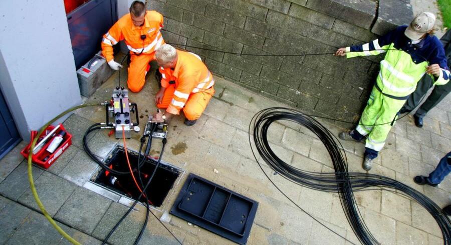 Når først rørene er lagt i jorden, er det nemt for teknikere at skyde (med lufttryk) fiberkabler til internetforbindelse gennem dem - som her tværs under en hel boligblok i Kolding. Arkivfoto: Claus Fisker, Scanpix