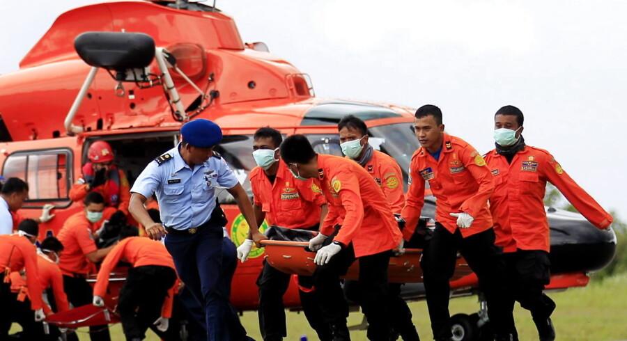 Redningshold bærer et af de fundne ofre væk fra en helikopter.