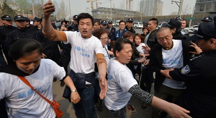 Vrede kinesiske pårørende til passagerer på det forsvundne fly fra Malaysia Airlines forsøger at fjerne en politibarrikade under en protest foran den malaysiske ambassade i Beijing tirsdag.