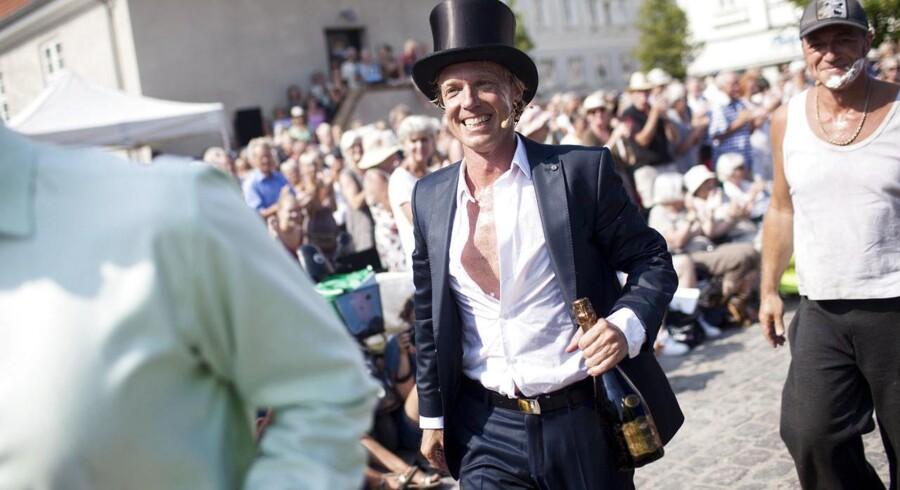 """Gert Henning-Jensen løber af scenen med champagne klar til fejring. Reportage fra åbningen af Copenhagen Opera Festival og premiere på Det Kongeliges opførelse af """"Barberen i Sevilla"""" på en ladvogn. Opførelsen foregik i sommerheden på pladsen foran Torvehallerne."""