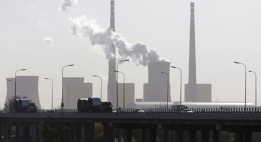 (FILES) This file photo taken on November 19, 2007 shows vehicles passing by a power plant in Beijing, as a water cooling tower emits a cloud of steam. The air has never been as polluted by carbon dioxide (CO2), the main greenhouse gas, as in 2015, with an average concentration of 400 ppm (parts per million) in the atmosphere, a symbolic threshold record, according to a report by the World Meteorological Organization (WMO) issued on October 24, 2016. The report was released before the negotiations on climate change, to be held in Marrakech (Morocco) from November 7 to 18, 2016. / AFP PHOTO / FREDERIC J. BROWN