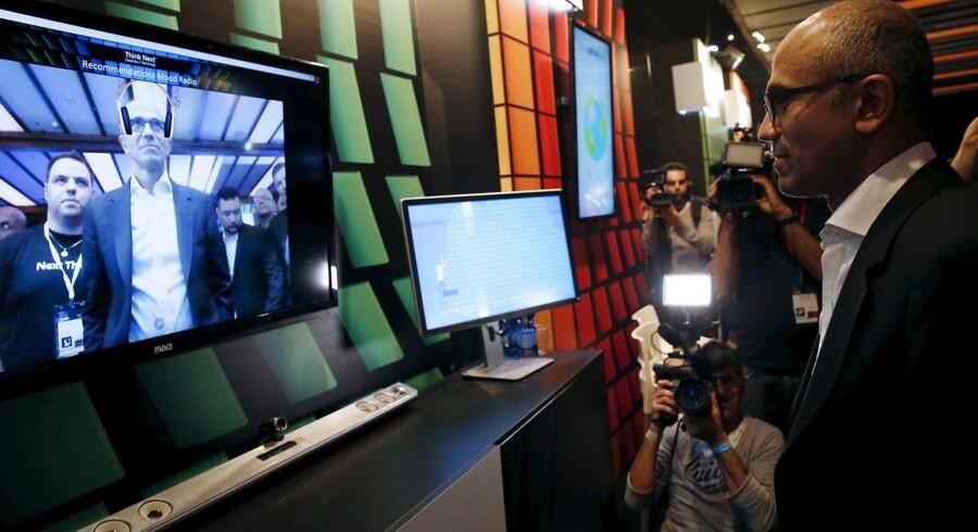 Microsofts topchef siden 2014, Satya Nadella (til højre og på skærmen), topper indkøbslisten for 2015 efter at have lagt forretningsplanen om for verdens største softwareselskab. Arkivfoto: Baz Ratner, Reuters/Scanpix