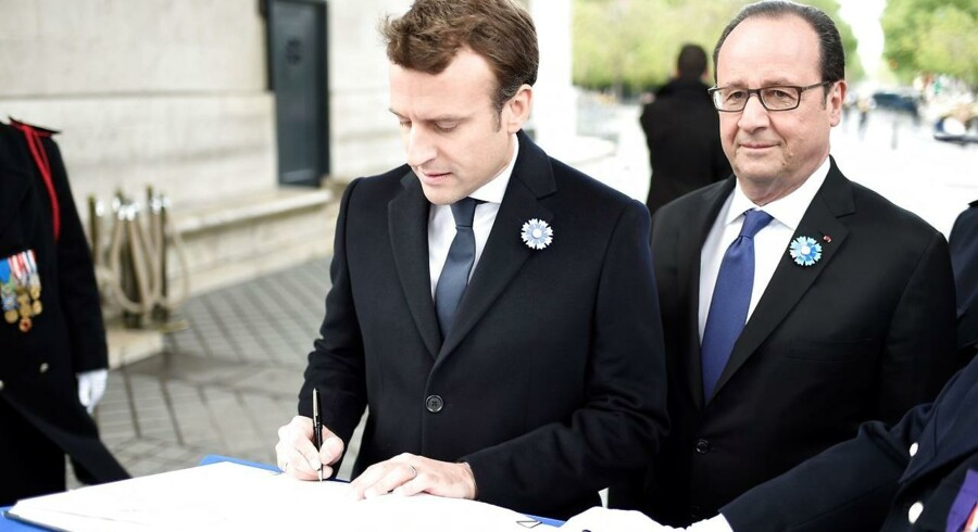 French president-elect Emmanuel Macron (L) flanked by outgoing French president Francois Hollande signs the remembrance book during the ceremony marking the 72nd anniversary of the victory over Nazi Germany during WWII on May 8, 1945 under the Arc de Triomphe monument in Paris on May 8, 2017. / AFP PHOTO / POOL / STEPHANE DE SAKUTIN