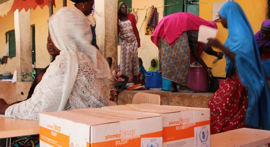 """A handout photo released by the World Food Programme (WFP) shows women sitting next to WFP-distributed specialized food to combat malnutrition in children at the Pompomari camp in Damaturu on January 26, 2017 during a visit by the WFP executive director. WFP executive director Ertharin Cousin is in Nigeria on a week-long trip to see programmes set up to stave off starvation caused by Boko Haram's Islamist insurgency. / AFP PHOTO / WFP / Andre VORNIC / RESTRICTED TO EDITORIAL USE - MANDATORY CREDIT """"AFP PHOTO / WFP / ANDRE VORNIC"""" - NO MARKETING NO ADVERTISING CAMPAIGNS - DISTRIBUTED AS A SERVICE TO CLIENTS"""