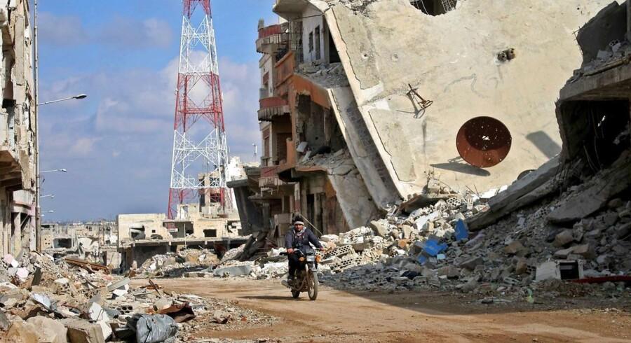 En syrisk mand på motorcykel kører forbi ødelagte bygninger i den sydlige by Daraa.