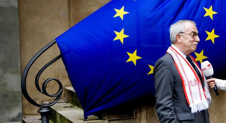 Uffe Ellemann-Jensen med roligan-halstørklæde foran et EU-flag...