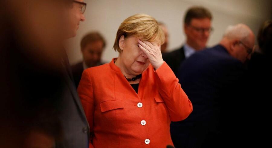 Den tysker kansler, Angela Merkel, tager sig til hovedet under et møde mandag med CDU og CSU i den tyske Bundestag.