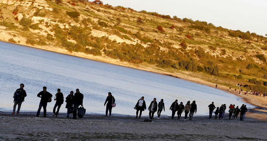 Refugees walk along a beach before trying to travel to the Greek island of Chios from the western Turkish coastal town of Cesme, in Izmir province, Turkey, in this March 5, 2016 file photo. To match EUROPE-MIGRANTS/TURKEY REUTERS/Umit Bektas