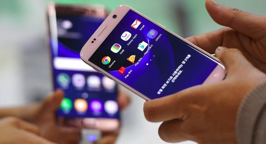 Samsungs storsælgende Galaxy S7 og S7 Edge har (her hvide) kanter på forsiden rundt om selve den trykfølsomme den af skærmen. De forsvinder i den nye Galaxy S8, som kommer til foråret, og som skal rejse Samsung igen oven på efterårets batteriskandale. Arkivfoto: Jung Yeon-Je, AFP/Scanpix