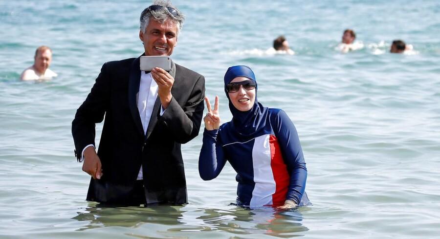 Rachid Nekkaz poserer sammen med en kvinde iført en såkaldt burkini ved stranden i franske Cannes.