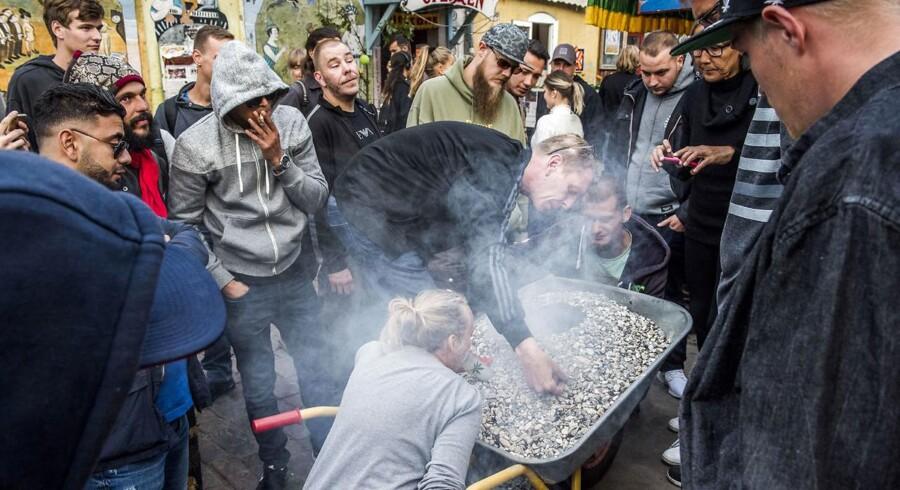 """En såkaldt jordfed går på omgang i Pusher Street på Christianias 45 års fødseldag mandag 26. september. """"100 g earth pipe"""", står der på et papskilt, der stikker op fra perlegruset i trillebøren. I midten brænder en bunke blandet hash, skunk og tobak. """"Om den rammer godt? Det er ren skævhed ned i lungerne, """" siger en ung skaldet fyr med et smørret grin. Han har lige taget et stort sug."""