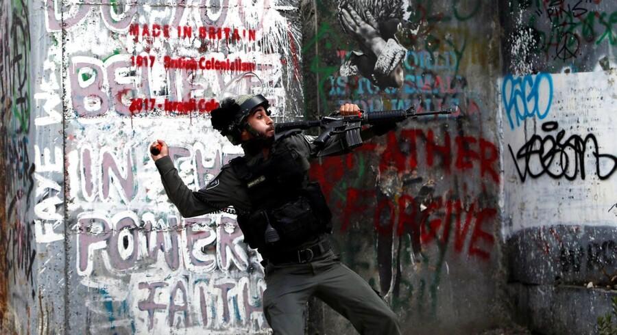En israelsk grænsebetjent kaster en grenat efter palæstinensiske demonstranter. REUTERS/Mussa Qawasma