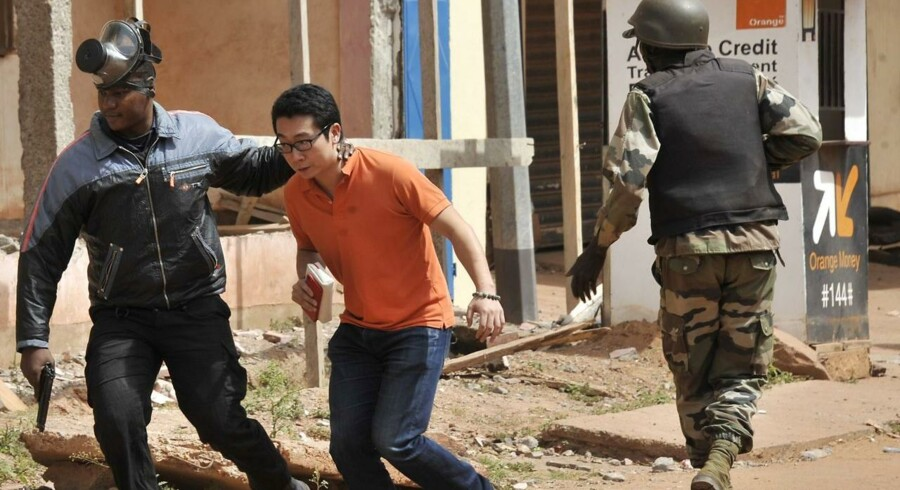 Sikkerhedsstyrker hjælper en mand væk fra Radisson-hotellet i Mali.