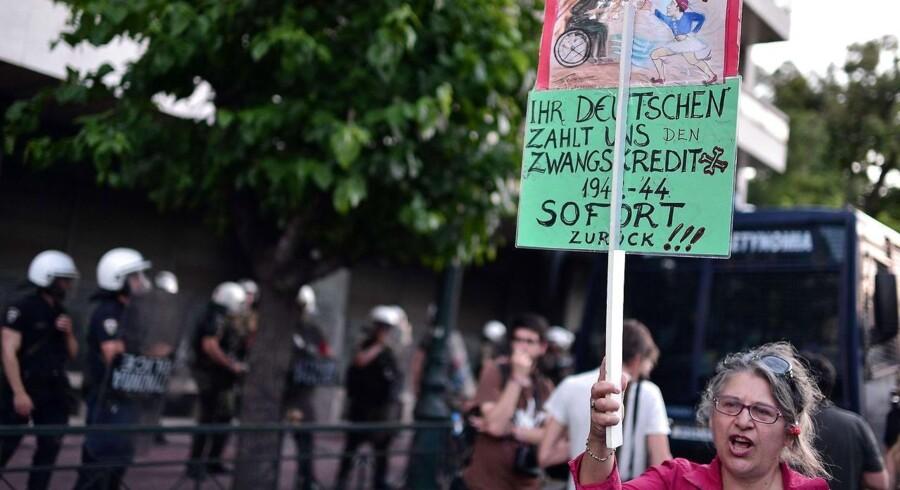 En kvinde demonstrerer foran Europa-Kommissionens kontorer i Athen. En række venstreorienterede grupper demonstrerede i slutningen af sidste uge mod EU-institutionerne - og i særdeleshed mod Tyskland. Grækerne har desperat brug for at få adgang til et lån på over 7,2 milliarder euro.