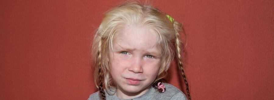 Den lille, ukendte pige kigger genert ind i kameraet på de billeder, der er offentliggjort i jagten på hendes forældre. Foto: Scanpix