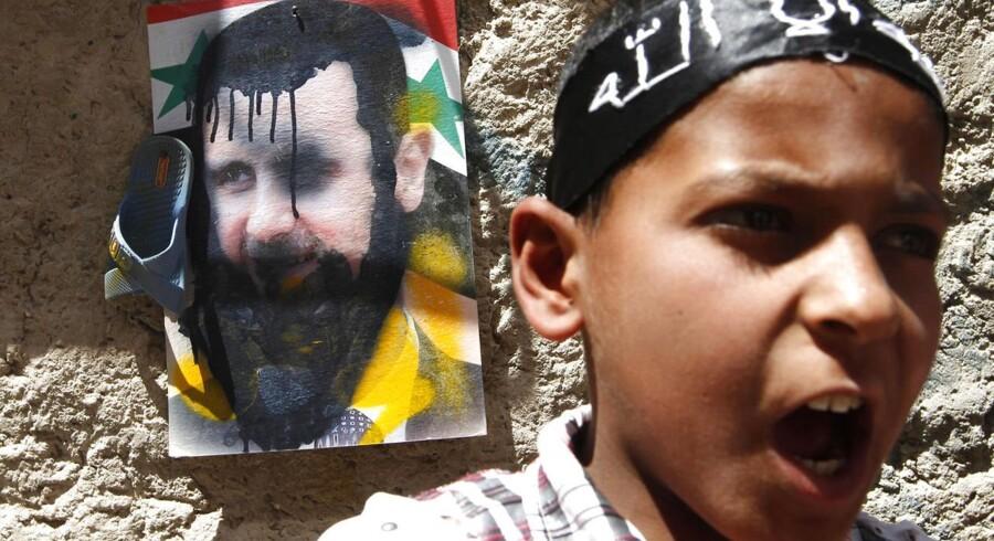 En syrisk dreng råber til en demonstration mod foran en skamferet plakat af Syriens præsident, Bashar al-Assad.