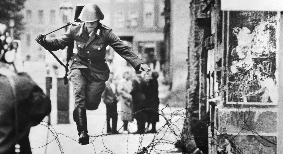Den 19-årige fuldtuniformerede politimand fra Østtyskland Conrad Schumann hopper over hegnet.
