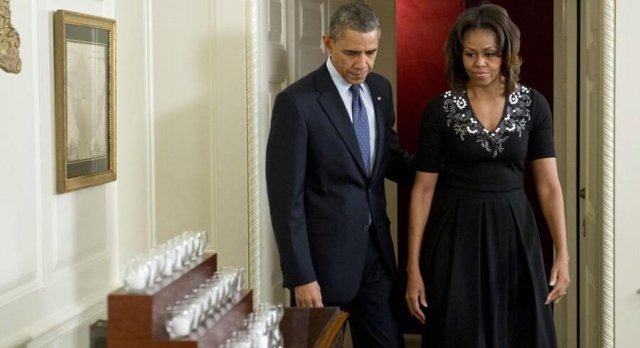 USAs præsident Barack Obama og hans hustru Michelle Obama tændte ved en mindehøjtidelighed I Det Hvide Hus 26 lys - et for hvert af ofrene for skolemassakren i Newtown for et år siden.20 børn og seks lærere blev dræbt i skoleskyderiet på Sandy Hook Elementary.