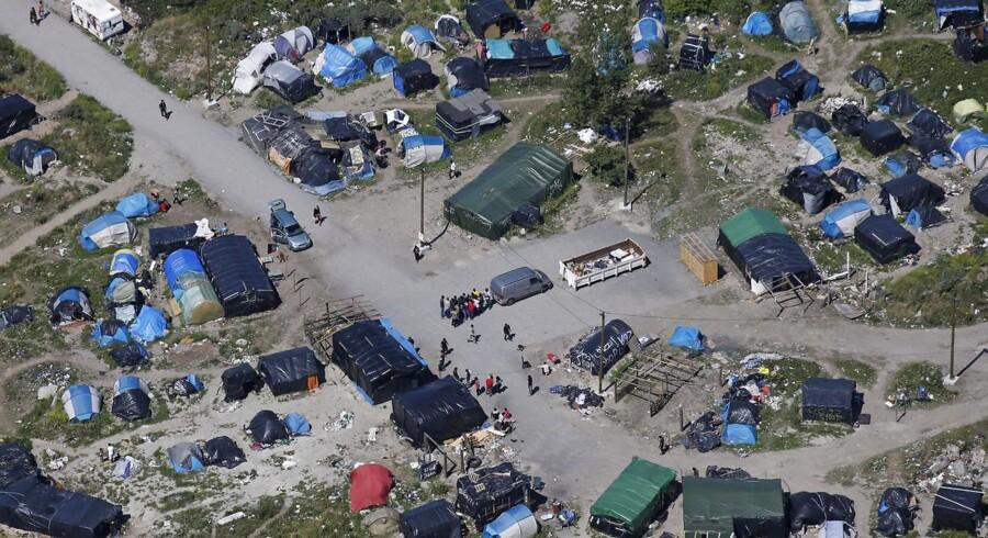 Migranterne har oprettet en interimistisk lejrby uden for Calais, mens de venter på at skaffe sig kørelejlighed over kanalen.