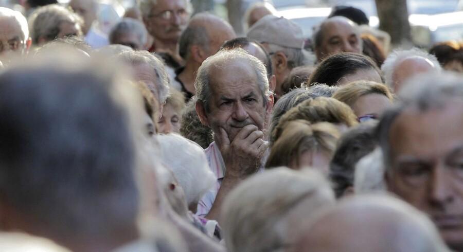 Græske pensionister, der ikke har hævekort til pengeautomater, står i kø for at få udbetalt dele af deres pension.
