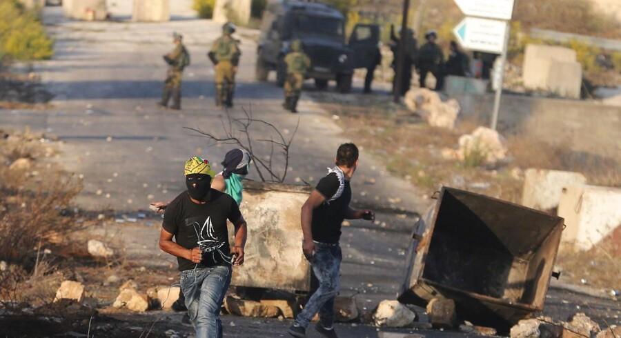 Palæstinensiske demonstranter i sammenstød med israelske tropper nær den jødiske bosættelse Beit El i nærheden af Ramallah på Vestbredden. 15. oktober 2015. 32 palæstinensere og syv israelere er blevet dræbt i løbet af de seneste to uger. Blandt de dræbte palæstinensere er ifølge israelsk politi 10 kniv-bevæbnede angribere såvel som børn og demonstranter, som er blevet dræbt af skud fra israelske styrker under de voldelige demonstrationer. REUTERS/Mohamad Torokman