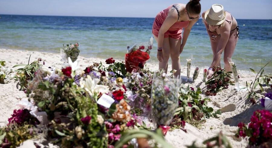 Turister lægger blomster på det sted, hvor en terrorist angreb turister i uskanten af byen Sousse.